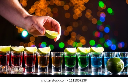 Alcoholic drink into small glasses on bar. Colorful cocktails at the bar. Colorful shots at the club. Alcoholic drink in different colors. Nightlife scene. Shots at the bar table.