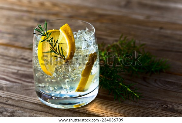 alcoholic drink with lemon and ice on a old wooden table