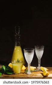 Alcoholic drink limoncello. Chilled glasses of Italian lemon liqour, fresh lemons and limoncello decanter on table.