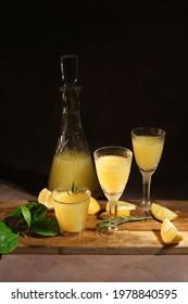 Alcoholic drink limoncello. Glasses of Italian lemon liqour, fresh lemons and limoncello decanter on table.