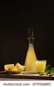Alcoholic drink limoncello on dark background. Shot glass of Italian lemon liqour, fresh lemons and limoncello decanter on table.