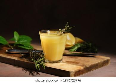 Alcoholic drink limoncello. Shot glass of Italian lemon liqour decorated rosemary, fresh lemons and limoncello decanter on table.