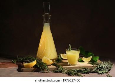 Alcoholic drink limoncello. Shot glass of Italian lemon liqour, fresh lemons and limoncello decanter on table.