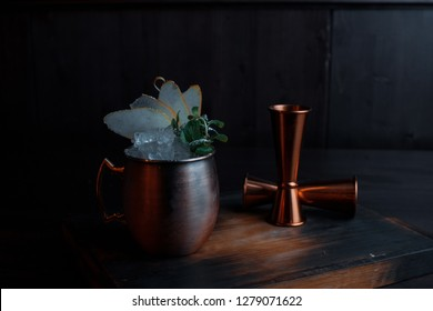 Alcoholic drink stands in a bronze metal mug on a table in a bar next to a metal jiggers.