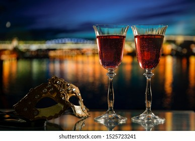 Alcoholic drinks. Carnival mask and two glasses of red wine against the backdrop of a bright night city