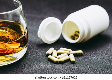 Alcoholic drinks and pills on table