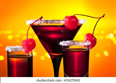 alcoholic drinks with sweet cherry on yellow background