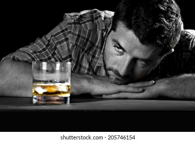 alcoholic drunk and wasted but attractive man sitting at table looking whiskey glass thinking in his alcohol addiction problem trying to avoid temptation and desire to drink in alcoholism concept