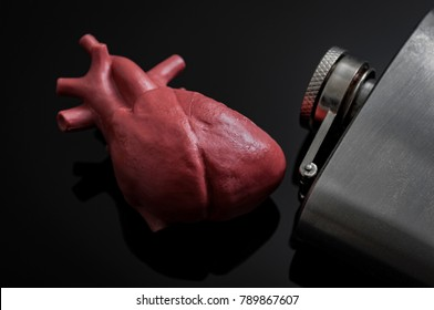 Alcoholic heart failure and damage or cardiomyopathy concept with a heart next to a metal flask of alcohol. Cardiomyopathy is a group of diseases that affect the heart muscle