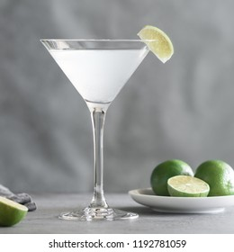 The alcoholic Kamikaze cocktail in a cocktail glass with a wedge lime on a table. Cocktail is made of equal part of vodka, lime juice and triple sec.