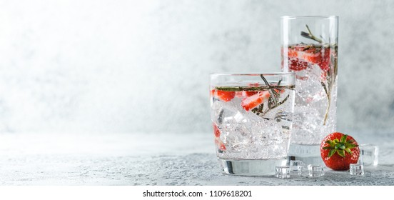 Alcoholic or non-alcoholic cocktail with strawberries and rosemary and ice in glass glasses. Free space for text. Banner Concept