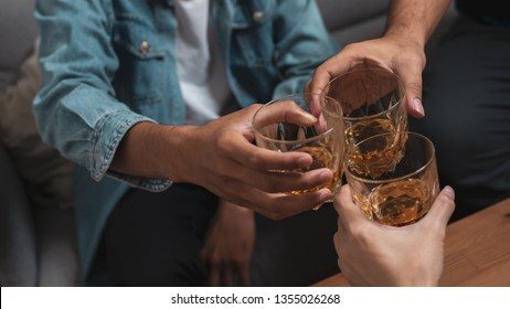 Alcoholic or party concept : Close up group of friend or colleague toasting glasses of alcohol whisky in pub or bar can use for party or celebrate concept.