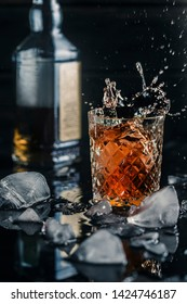 alcoholic whiskey drink in an ice glass with a bottle in the background, on a black background, close-up with splashes