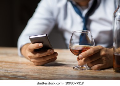alcoholism, alcohol addiction and technology concept - close up of male hands with smartphone and glass of brandy