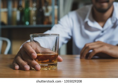 Alcoholism or Alcoholic concept : Close up young Asian guy drinking alcohol alone in pub or bar because life problem or stress.