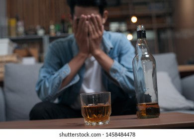 Alcoholism or Alcoholic concept : Close up young Asian guy feeling depressed drinking alcohol alone in pub or bar because life problem or stress.