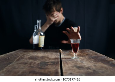 Alcoholism concept. The man fights against alcohol. Against a dark background