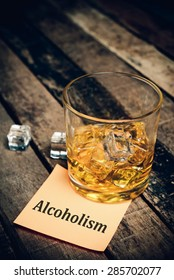 alcoholism with label on paper note. Glass of scotch whiskey