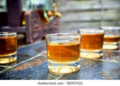 Alcohol,taste and drink concept-glasses with whiskey,old glass barrel on stone table and wooden background.