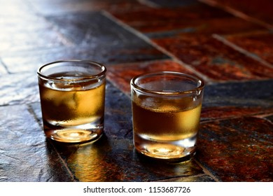 Alcohol,taste and drink concept-two glasses of whisky on a old stone table.