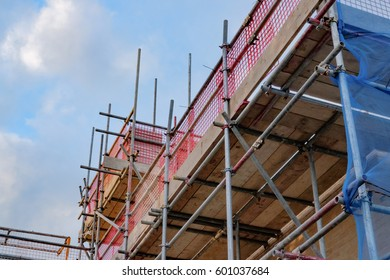 ALCONBURY, CAMBRIDGESHIRE, UK - CIRCA MARCH 2017: Scaffolding seen assembled around residential houses being built at a former RAF base, showing various health and safety measures imposed.