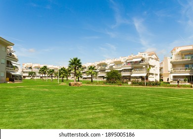 Alcossebre, Castellon province, Valencian Community, Spain - August 2020. Beautiful holiday resort complex with a vibrant lawn and palm trees. Al Cala Blau residence.