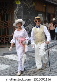 ALCOY, SPAIN - SEPTEMBER 21, 2019: Couple dressed in late 19th/20th century attire walking cobblestone street at Alcoy's 3rd annual Modernist Fair cultural event.
