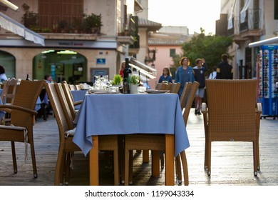 ALCUDIA, MAJORCA, SPAIN - October 2nd, 2018: Restaurants tables are set for an evening meal in old town of Alcudia