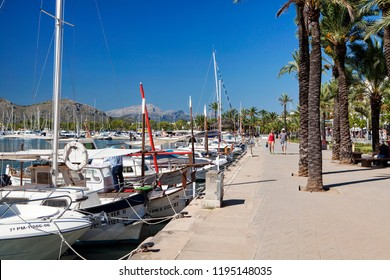 ALCUDIA, MAJORCA, SPAIN - September 23rd, 2018: Promanade along marina.  Port d'Alcudia  is a popular resort town and holiday destination on the northeast coast of Majorca.