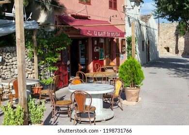 ALCUDIA, MAJORCA, SPAIN - September 24rd, 2018: Tables and chairs placed outside typical Spanish restaurant in old town of Alcudia