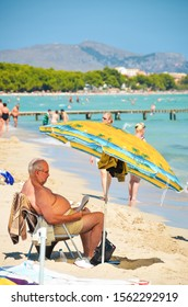 Alcudia, Spain 14.09.2011 - Older overweight man reading a newspaper at sandy beach under umbrella. People sunbathing at Playa de Muro. Mallorca island famous tourist destination.