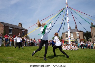 Aldborough, North Yorkshire United Kingdom - May 8 2016: At the annual May day event children dance around the May pole using ribbons in traditional dances to celebrate May Day