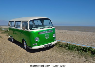 ALDEBURGH, SUFFOLK, ENGLAND - APRIL 19, 2014 : Classic Green and White Volkswagen Camper van parked at Aldeburgh Beach on a sunny day.