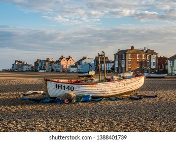 Aldeburgh, Suffolk, England, Britain, July 2018, evening summer golden light on small fishing boat on shingle beach with traditional seaside houses