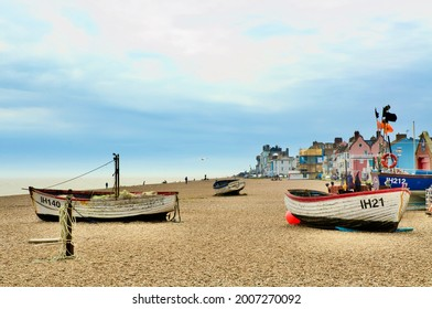 Aldeburgh, Suffolk, UK - 10 May, 2021:  Three boats stand on the beach set against the houses of Aldeburgh.
