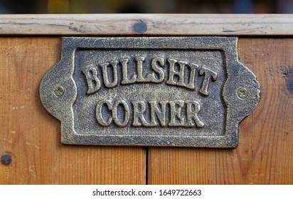 Aldeburgh, Suffolk. UK. June 2nd 2018. Brass plaque on wooden panel in the White Hart pub, saying 'Bullshit Corner'.