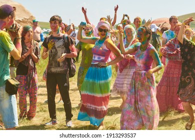 Aleksandrovsky, Russia 2015.06.21 Cheerful crowd of happy European people of Hare Krishnas whose body and face are covered with colored paint dancing and having fun at Holi