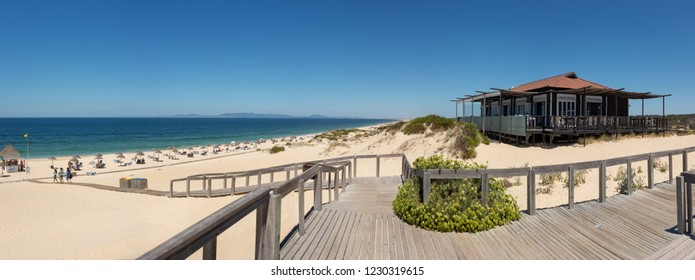 ALENTEJO, PORTUGAL - JULY 28, 2015: Restaurante Sal overlooking the beach at Praia do Pego, Carvalhal, Portugal. The wooden boardwalk leading down the beach is in the foreground