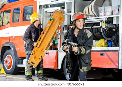 Alert male firefighter holding hose while colleague carrying wooden stretcher by truck at fire station