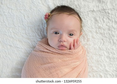 Alert month old baby girl swaddled in a peach colored wrap. Shot in the studio on a white blanket.