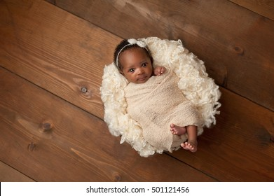 An alert, one month old baby girl wearing a cream colored bow headband. She is swaddled with a beige wrap and is looking directly into the camera. Shot in the studio on a wood background.