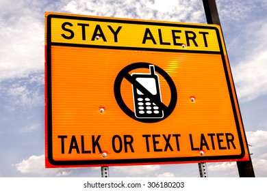 Alert sign in neon yellow and orange, against a bright cloudy sky, warning drivers not to text or talk while driving