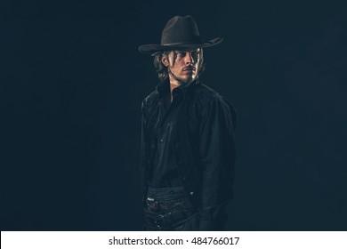 Alert vintage 1900 cowboy looking over shoulder. Studio shot.