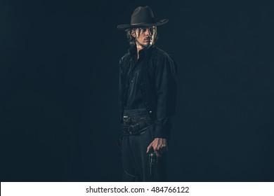 Alert vintage 1900 cowboy standing with gun. Studio shot.