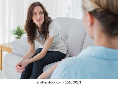 Alert woman sitting with her therapist talking to her in a private session