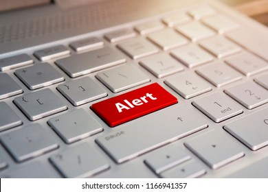 alert word on red keyboard button. Color button on the gray silver keyboard of modern ultrabook. caption on the button