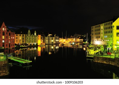 Alesund, Norway - August 11, 2010: Beautiful Alesund Marina night view with yachts, illuminated nouveau houses and reflections in the water.