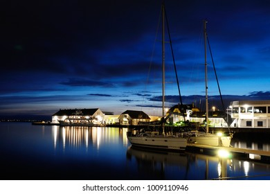 Alesund, Norway - August 11, 2010: Beautiful Alesund port night view with yacht and reflections in the water