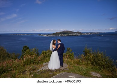 Alesund, Norway - June 11, 2017: Wedding photo session in Alesund, Norway. Two happy people standing on a rocks.