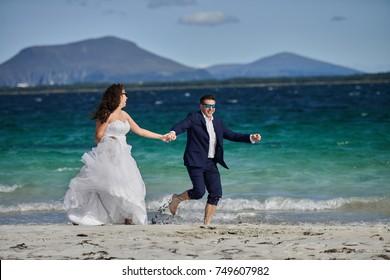 Alesund, Norway - June 11, 2017: Wedding photo session in Alesund, Norway. Two happy people walking on the beach